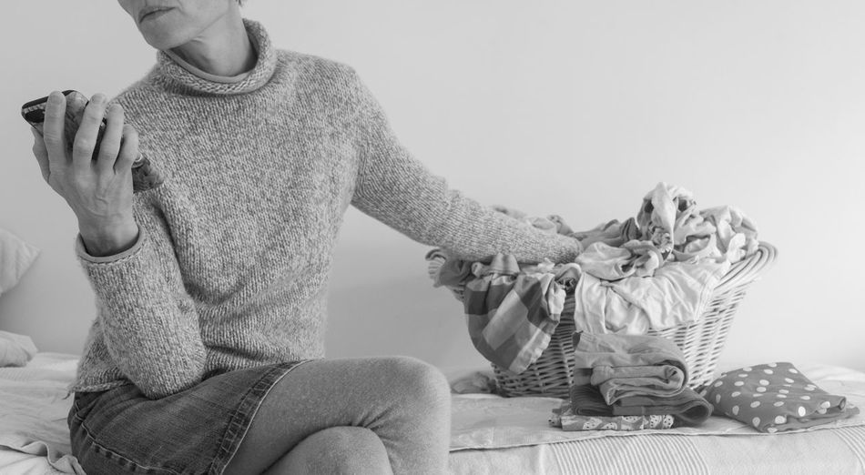 Woman using smart phone while folding laundry (black and white) Black & White Laundry Woman Adult Casual Clothing Front View Furniture Hand Holding Home Interior Human Hand Indoors  Leisure Activity Lifestyles One Person Real People Relaxation Representation Sitting Studio Shot
