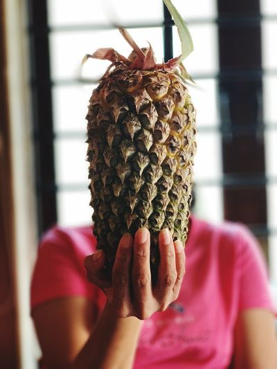 Woman with face covered by pineapple