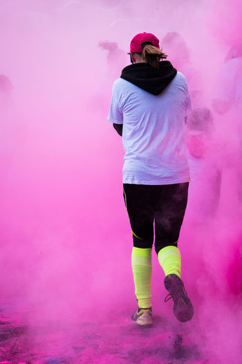 Rear view of woman walking on road in pink powder paint