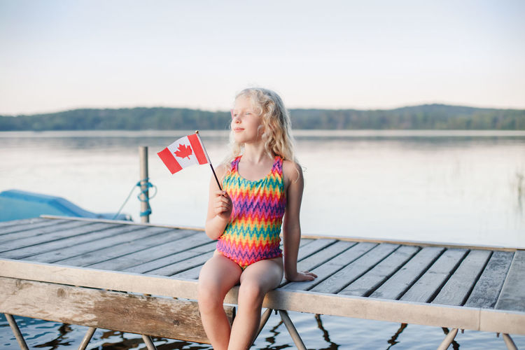 Happy caucasian girl sitting on pier by lake and waving canadian flag. kid celebrating canada day