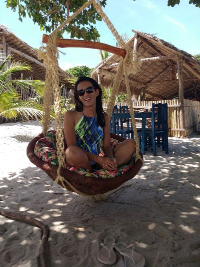 Portrait of smiling young woman sitting on swing at beach