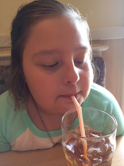 Close-up of girl drinking ice tea at home