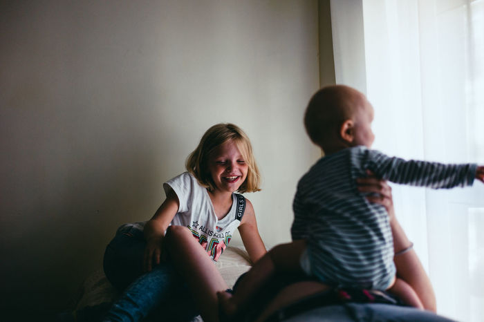 Cheerful girl with brother sitting on bed at home