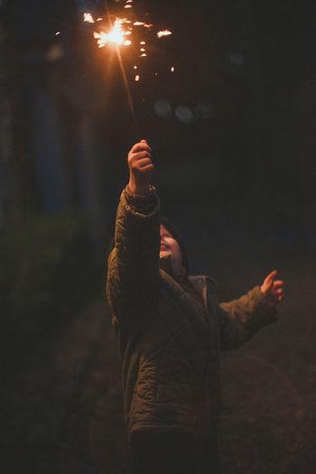 Boy celebrating holding illuminated sparkler in air