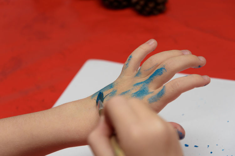 Cropped image of boy coloring hands on table