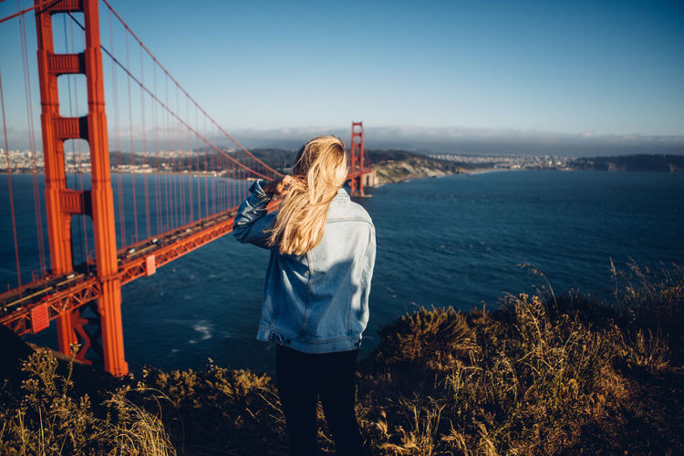 Rear view of woman standing by suspension bridge against sky