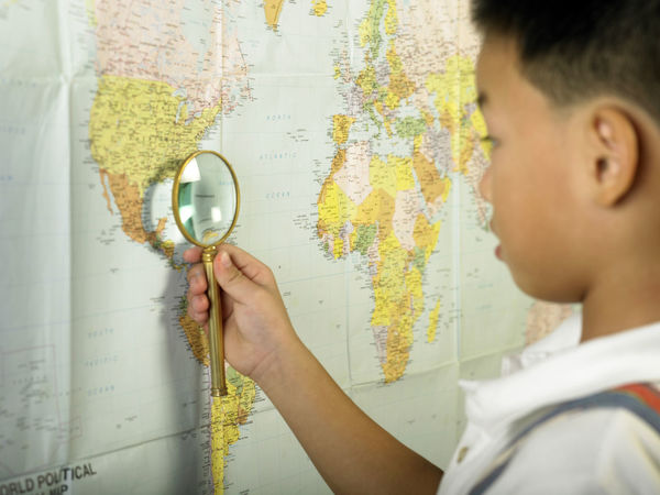 boy holding a magnifier glass on the world map Enlarge Exploring Map Close-up Day Discovery Education Examining Focus Headshot Holding Indoors  Learning Magnifier Magnifying Glass Map One Person Real People Search Searching Student World Map