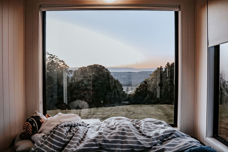 Rear view of woman sleeping on bed against landscape