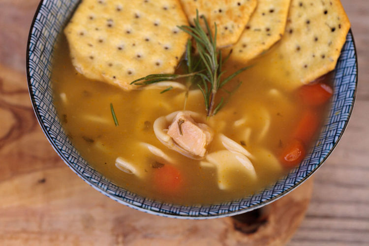 Chicken noodle soup in a blue and white bowl with crackers, all sitting on a wood cutting board. Broth Chicken Noodle Soup Chicken Soup Chicken Soup ... Comfort Food Crackers Cutting Board Food Food And Drink Home Remedies Indoors  No People Rustic Soup Wood