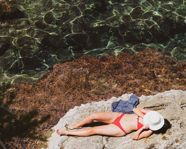High angle view of woman lying on rock