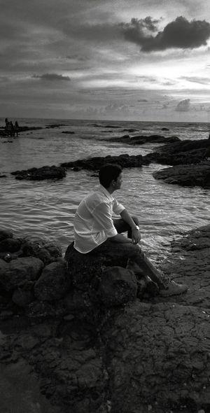 Man Sitting On Rock At Seashore