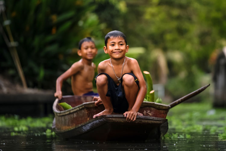 Portrait of shirtless boys sitting on boat in river