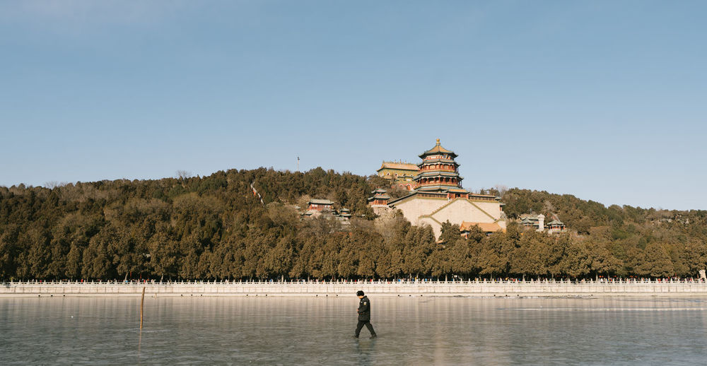 Walking on the Kunming Lake Architecture Day Full Length History Landscape One Person Outdoors People Place Of Worship Sky Tradition Travel Travel Destinations Water Winter
