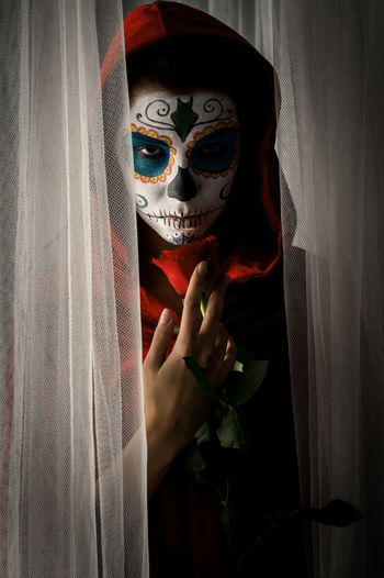 Portrait Of Woman With Halloween Make-Up Holding Rose While Standing Amidst Curtains