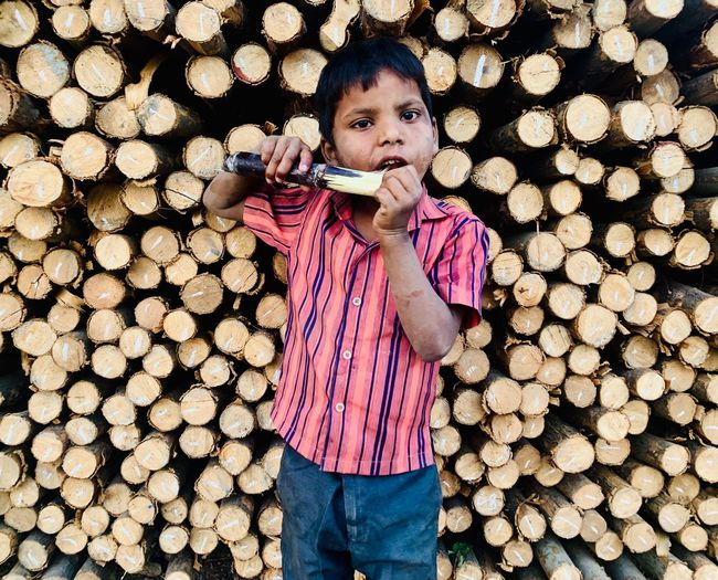 Portrait Of Boy Eating Sugar Cane While Standing Against Logs