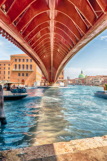 VENICE, ITALY - APRIL 29: Underneath the controversial Constitution Bridge in Venice, Italy on April 29, 2018. Designed by the starchitect Santiago Calatrava, the bridge opend in 2008 Arch Arch Bridge Architecture Bridge Bridge - Man Made Structure Building Building Exterior Built Structure Canal City Cityscape Connection Day Mode Of Transportation Nature Nautical Vessel No People Outdoors Sky Tourism Transportation Travel Travel Destinations Water Waterfront