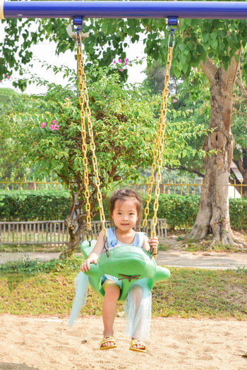Portrait of a smiling girl on swing
