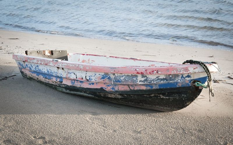 Abandoned boat moored on beach
