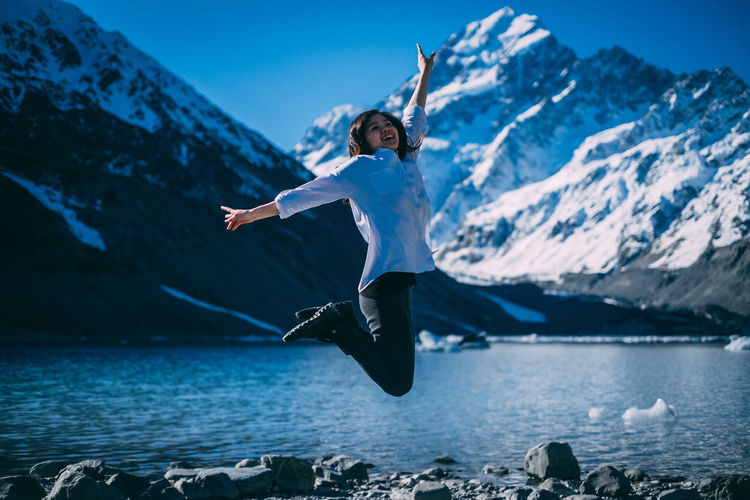 Young girl  jumping on mountain against sky