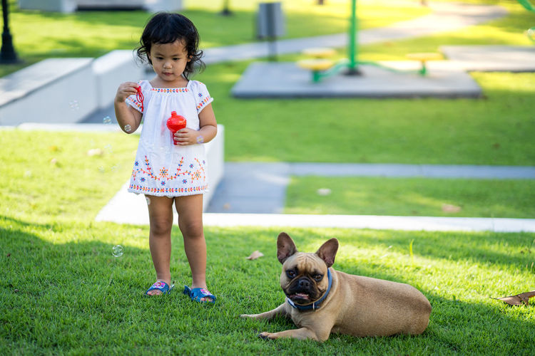 Girl blowing bubbles while standing by dog at park