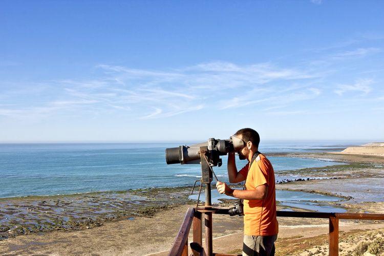 Side view of mature man using binoculars at beach against sky