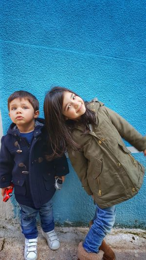 Siblings standing against blue wall