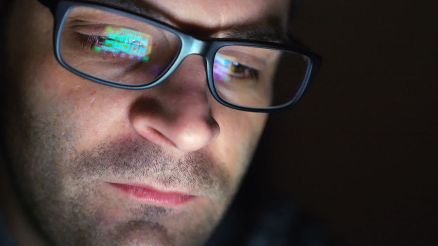 Close-up of man wearing eyeglasses with reflection