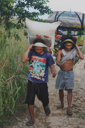 Bonding Burden BYOPaper! Casual Clothing Day At Work Field Friendship Front View Full Length Grass Lifestyles Load Men Carrying Heavy Men Carrying Sack Outdoors Real People The Photojournalist - 2017 EyeEm Awards Two People Workers Working Hard
