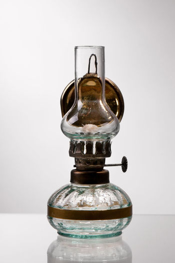 Single retro styled glass decorative oil lamp standing on glass table surface and gray background, object in vertical orientation, nobody. Alternative Antique Brass Decoration Decorative Glass Gray Background Lamp Lantern Light Lighting No People Oil Old Paraffin Retro Studio Shot Transparent Vintage Wick