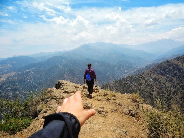 Cropped hand of person with woman on mountain against sky