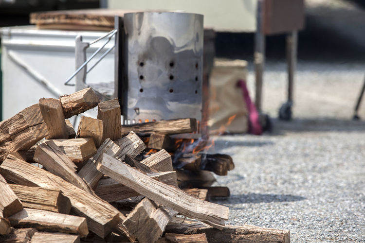 Close-up of firewood by camping stove on field during camping