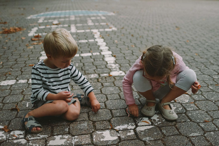 High angle view of siblings playing on cobblestone