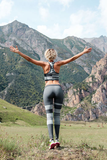 Rear view of woman with arms outstretched standing against mountains