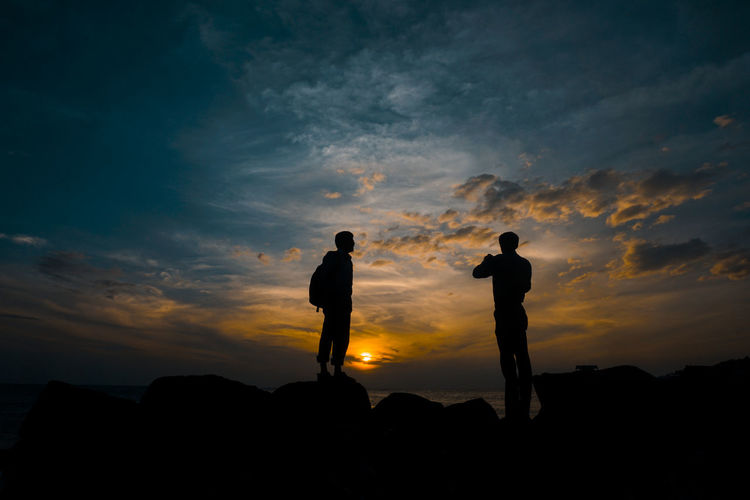 Silhouette Friends Standing On Rock Against Sky During Sunset