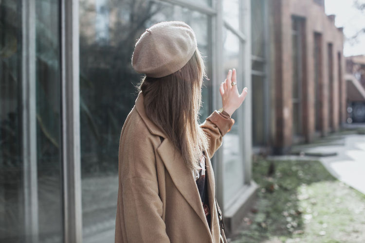 Side view of young woman waving by building