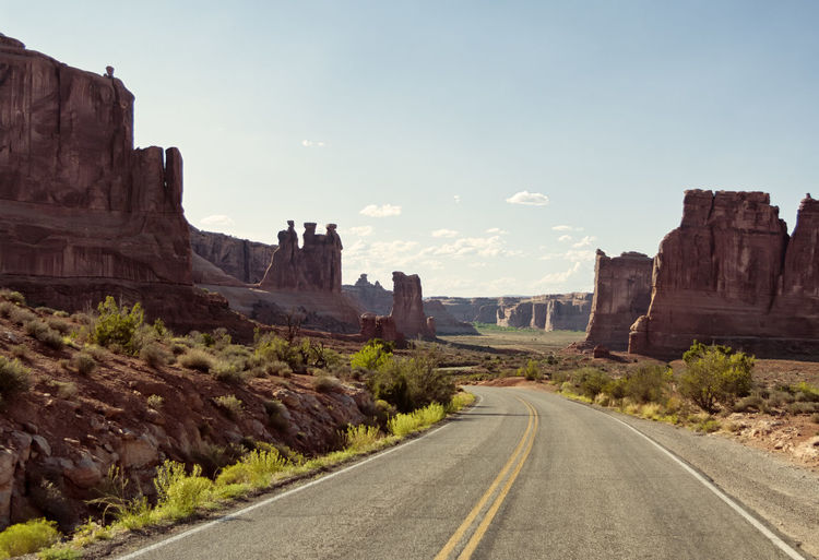 Vintage toned picturesque American desert highway in daylight with clear sky for copyspace. Concept for travel and freedom American Asphalt Desert Driving Freedom Speedway Travel USA Adventure America Arid Daylight Dry Freeway Highway Landscape Lane Nature No People Outdoors Remote Road Rocks Valley Vintage
