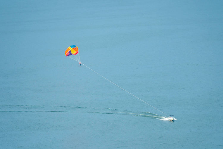 Adventure Blue Day Extreme Sports Flying Horizon Over Water Leisure Activity Mid-air Nature Outdoors Parachute Paragliding Parasailing Real People Sea Sky Sport Transportation Unrecognizable Person Water Waterfront