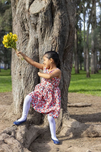 Full length of smiling girl by tree trunk