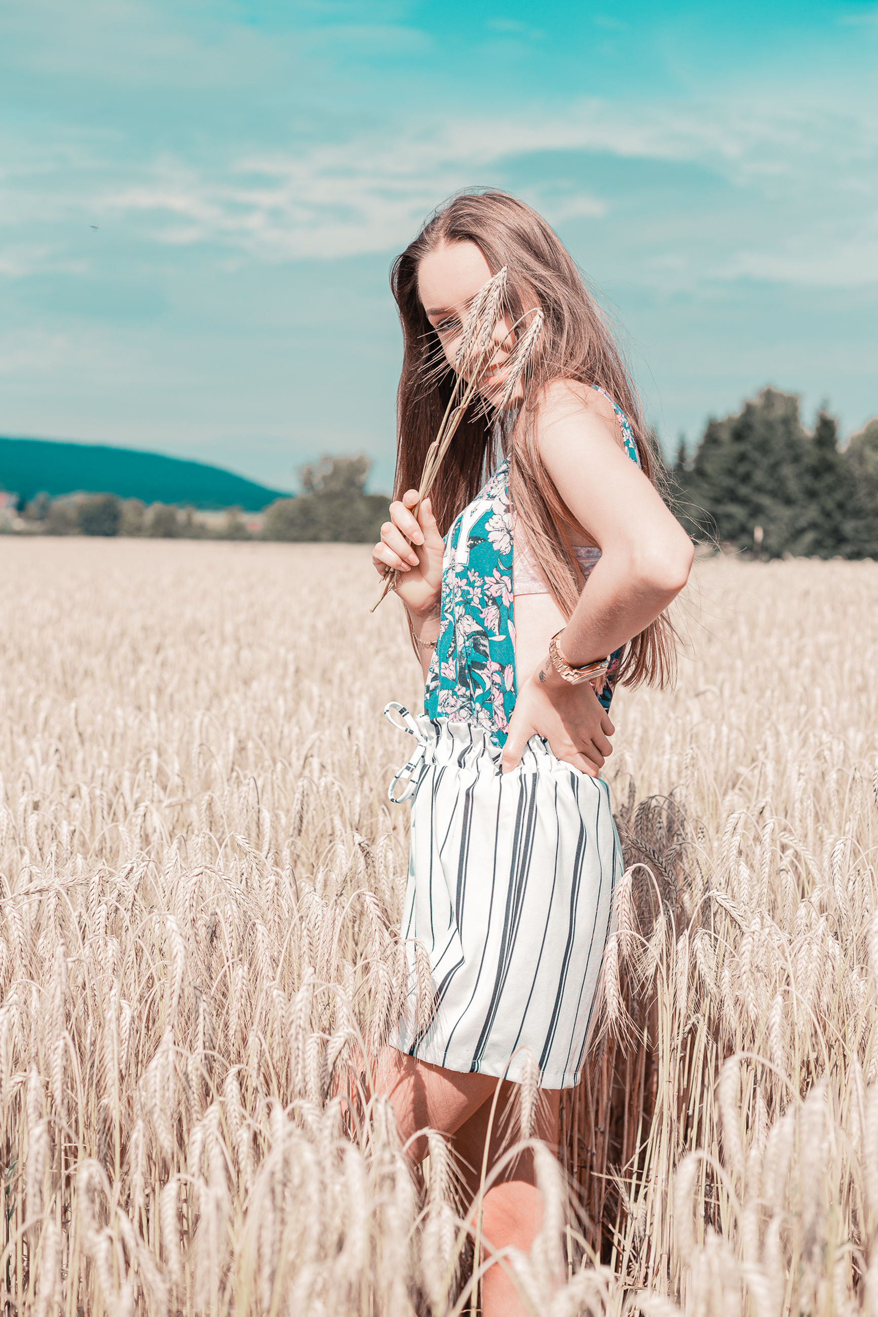 one person, field, land, agriculture, real people, crop, lifestyles, women, leisure activity, long hair, hair, plant, nature, cereal plant, farm, landscape, hairstyle, day, casual clothing, beautiful woman, outdoors