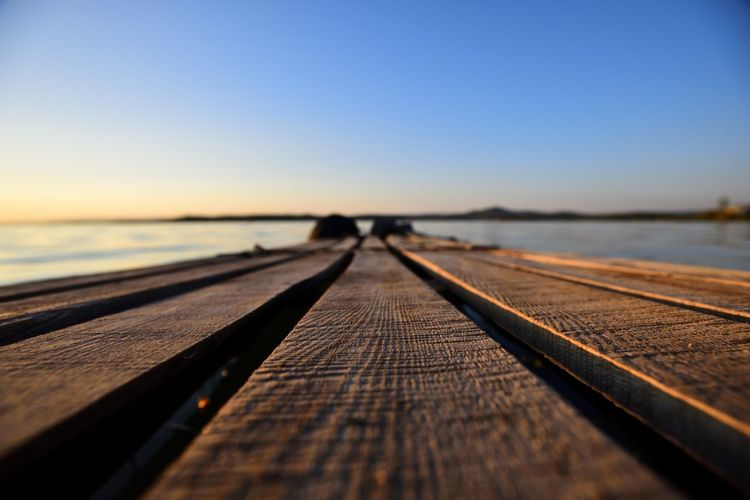 Clear Sky Diminishing Perspective Direction Horizon Horizon Over Water Land Nature Outdoors Pier Scenics - Nature Sea Selective Focus Sky Sunlight Sunset Surface Level The Way Forward Water Wood Wood - Material