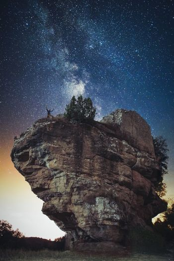 Low angle scenic view of star field over rock formation against sky at night