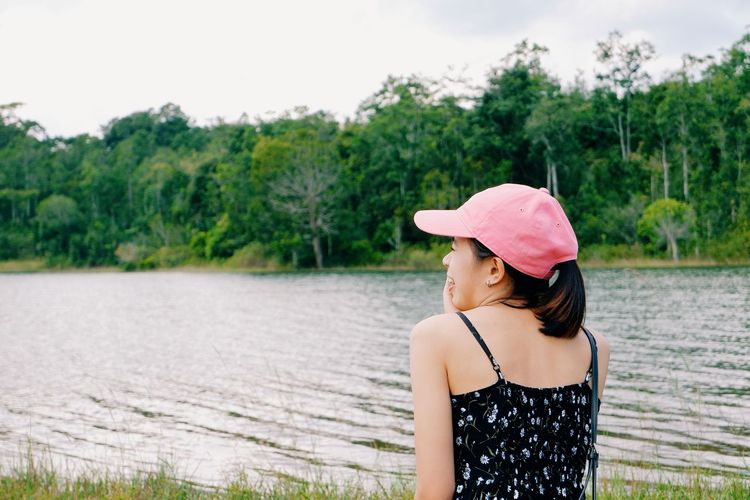 Woman standing by pink lake against trees