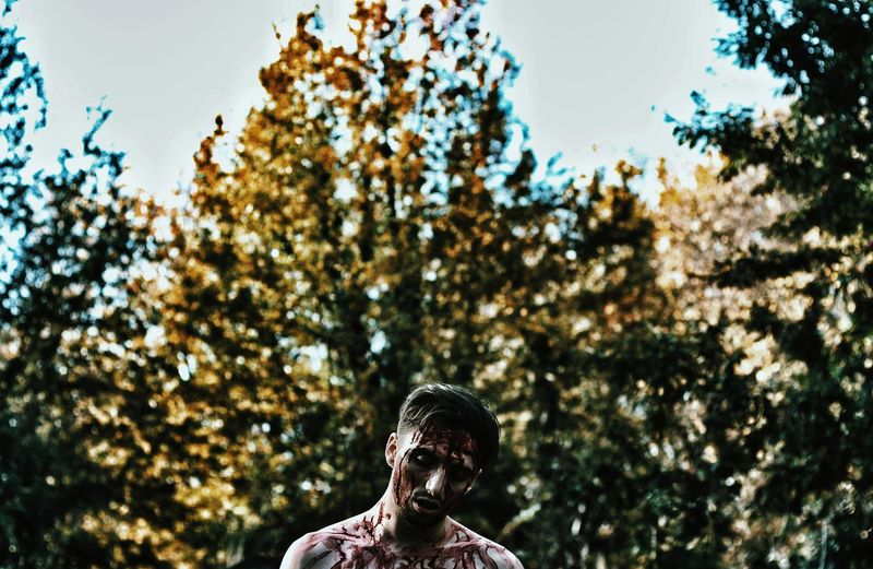 Low Angle View Of Man Covered In Blood Against Trees