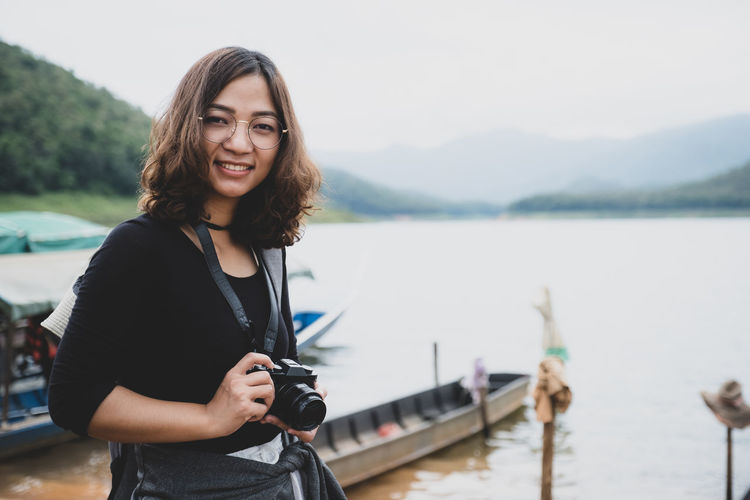Portrait of beautiful young woman standing against lake