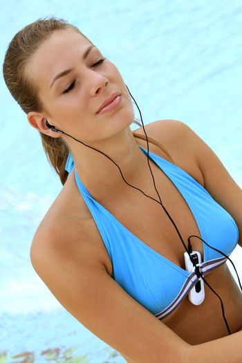 young blond woman listening to music with MP3 players at the pool Beautiful Happy Holiday Listening Music Music Summer Holidays Woman Beautiful Woman Beauty Bikini Blond Girl Happyness Leisure Leisure Activity Lifestyles Mp3 Player One Person Pretty Relaxation Swimming Pool Vacation Water Wellbeing Young Adult