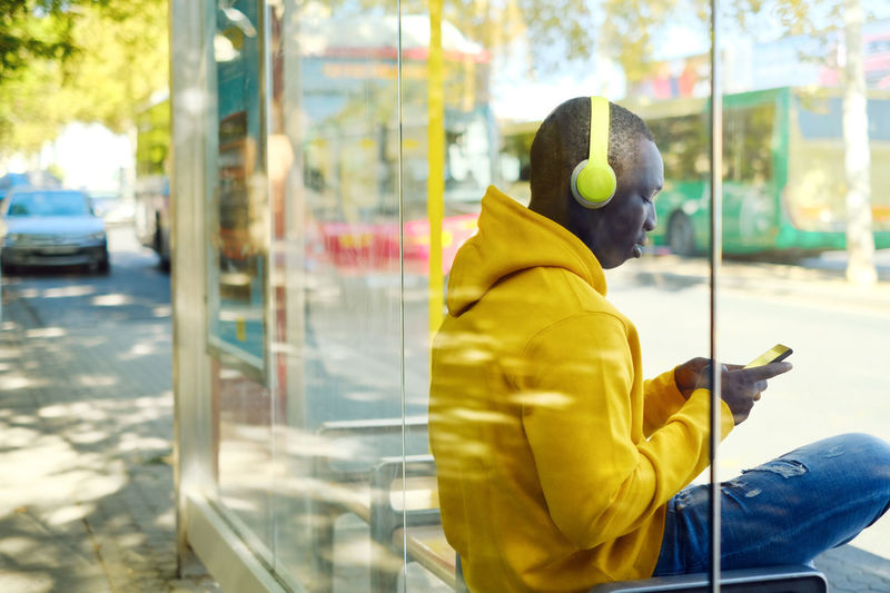 Man listening music while sitting at bus stop