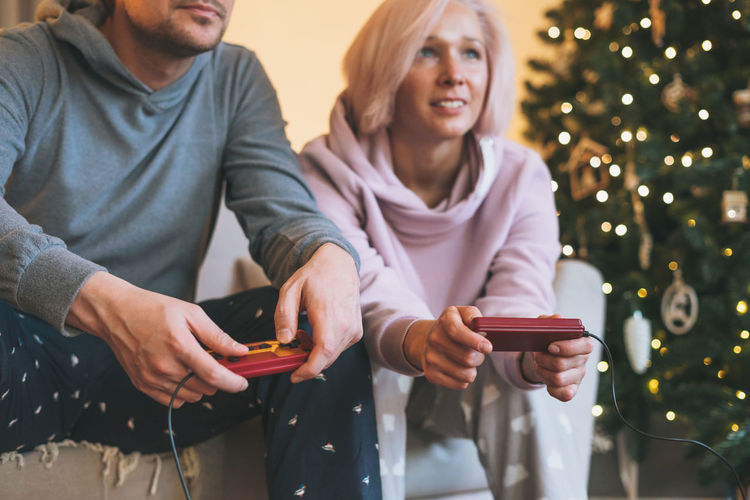 Crop photo of young family in home clothes playing video games on couch on background