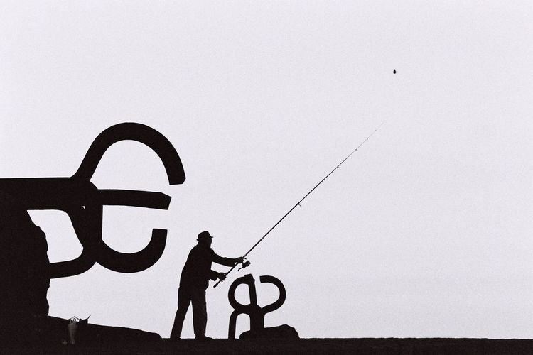 Low angle view of silhouette man with fishing rod against clear sky at dusk