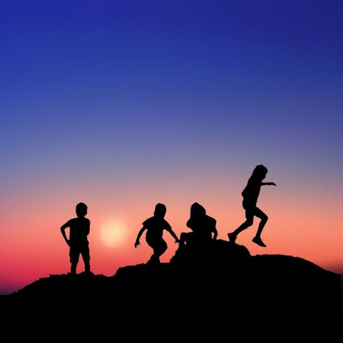 Silhouette children playing on rock against blue sky during sunset