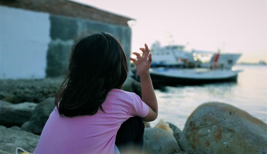Rear view of young woman on rock at sea